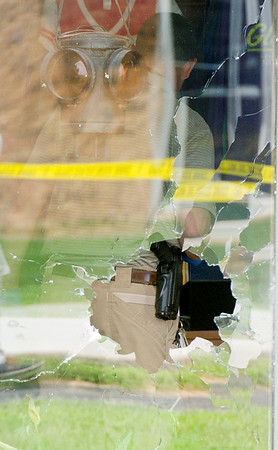 An investigator can be seen through shattered glass as he investigates a shooting on Monday morning at Prairie Mountain in Lockwood. Two employees of the company were injured during the shooting.<br /> Globe | Laurie Sisk