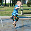 Globe/Roger Nomer<br /> Liam Simpson, 2, Joplin, jumps in the water on Wednesday at the splash pad at Parr Hill Park.