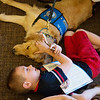 Globe/Roger Nomer<br /> Dalton Thomas, 9, lies next to Olive the comfort dog on Sunday at Immanuel Lutheran Church. Seven comfort dogs visited the church after Saturday's shooting injured members and comfort dogs.