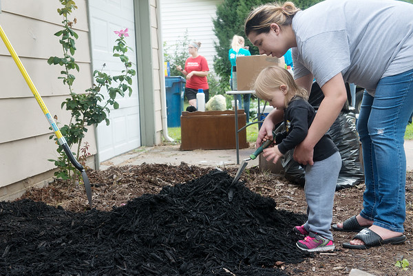 Globe/Roger Nomer<br /> Danielle Turner helps her daughter Autumn, 2, with mulch on Wednesday as Brush of Kindness volunteers at their home in Carl Junction.