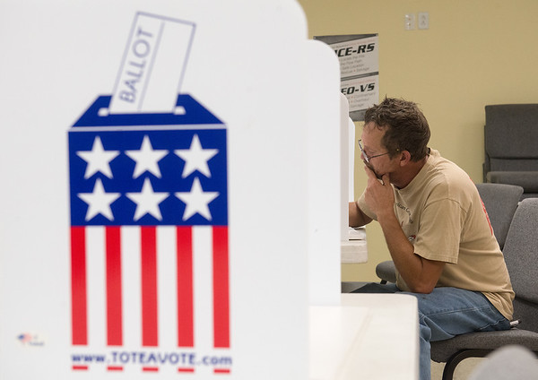 Globe/Roger Nomer<br /> Marlon Oxford votes during Tuesday's primary at the Redings Mill Fire Department.