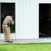 An investigator works the scene of a shooting on Monday morning at Prairie Mountain in Lockwood. Two employees of the company were injured during the shooting.<br /> Globe | Laurie Sisk