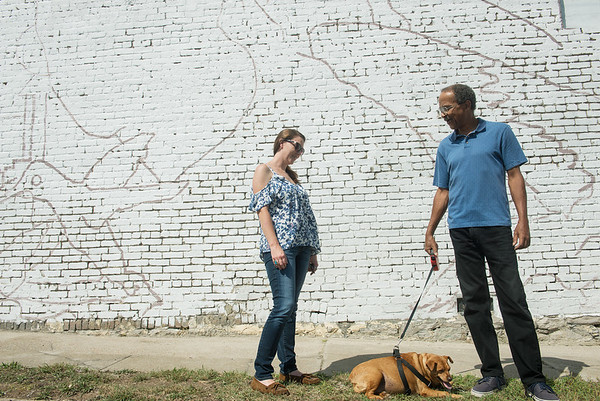 Globe/Roger Nomer<br /> Jenny Journeycake, mural artist, talks with Marvin McMillan and his dog Nellie in front of the East Town mural on Wednesday.