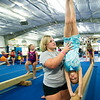 Payton Johnson, gymnastics coach at The Flip Shop, spots Isabella Baumgardner on the balance beam during classes on Wednesday night at the gym.<br /> Globe | Laurie Sisk