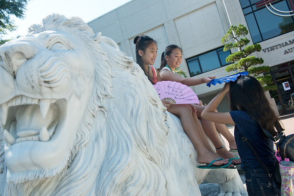 Globe/Roger Nomer<br /> (from left) Marie Nguyen, 14, Eagan Minn., Christine Ta, 12, Tampa, Fla., and Trinh Nguyen, 14, Eagan, Minn., cool off in the shade on Thursday at Marian Days in Carthage.
