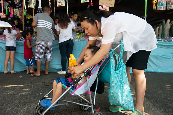 Globe/Roger Nomer<br /> Haylie Nguyen, New York, helps her son Cyrek Vo Nguyen, 3, stay cool with a fan on Thursday at Marian Days in Carthage.