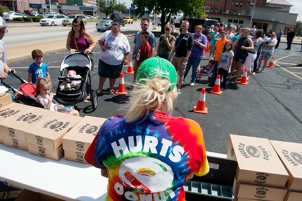 Globe/Roger Nomer<br /> Kass Clegg helps customers as they line up on Wednesday for Hurts Donuts at Memorial Hall. A portion of the sales from the Springfield donut shop's visit to Joplin will go to Children's Haven.
