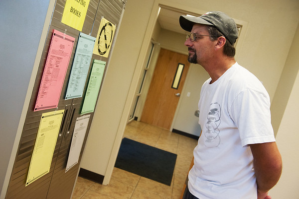 Globe/Roger Nomer<br /> Tom Souder examines the sample ballots during Tuesday's primary at the Housing Authority of Joplin.