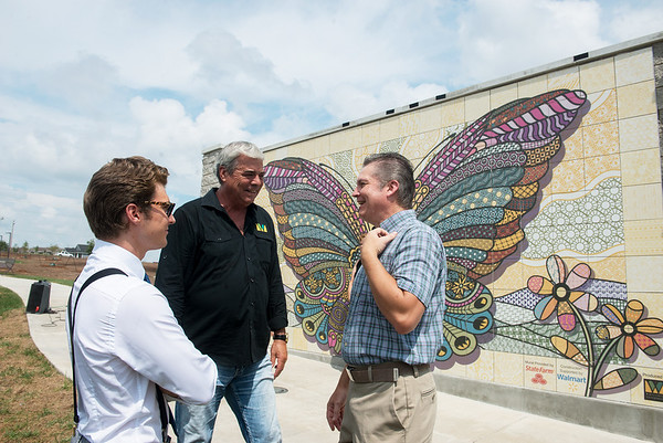 Globe/Roger Nomer<br /> Jordan, left, and AJ Wood, designers of the butterfly mural, talk with Paul Whitehill, owner of Whitehill Enterprises, center, on Wednesday at the mural unveiling in Mercy Park.