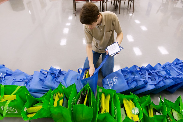 Globe/Roger Nomer<br /> Ethan Samford helps assemble gift bags for police officers and their spouses on Tuesday at St. John's Lutheran Church.