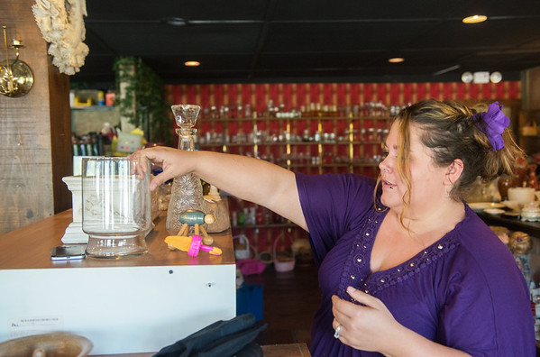 Globe/Roger Nomer<br /> April Brummitt, co-owner of Penny Pinchers, stocks items on Wednesday. The store is across the street from the East Town mural.