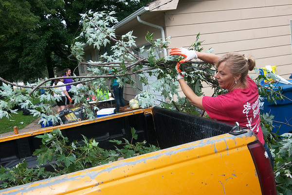 Globe/Roger Nomer<br /> Julie Maus loads limbs on Wednesday while volunteering with Brush of Kindness in Carl Junction.