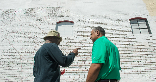 Globe/Roger Nomer<br /> Deon Anderson, a member of the design team, left, talks with William Kean, co-owner of MEs Place, about the design of the East Town mural on Wednesday.