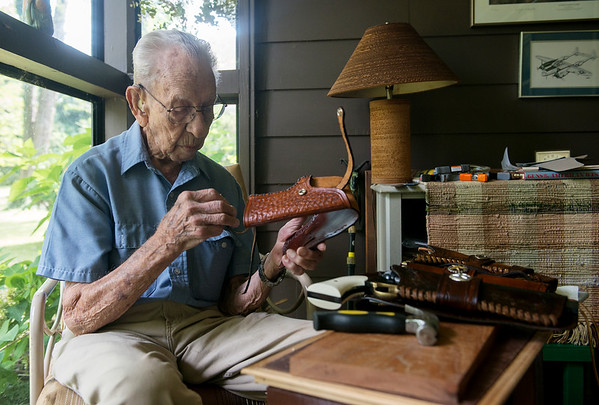 Globe/Roger Nomer<br /> Neal Ruff works on a leather holster on Tuesday morning.