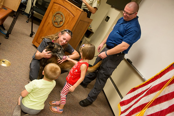 Globe/Roger Nomer<br /> Pam Helm, veterinarian at Main Street Pet Car, Charlotee Todd, 4, and Tyler Talkington, 4, congratulate Jasper County Sheriff K-9 Lyssa on her retirement on Friday. Also pictured is Lyssa's handler Cpl. Matt Smith, who said Lyssa has tracked about 60 suspects and 30 missing children over her eight-year career. Main Street Pet Care also presented the department and the Joplin Police Department with K-9 cooling vests for their dogs.