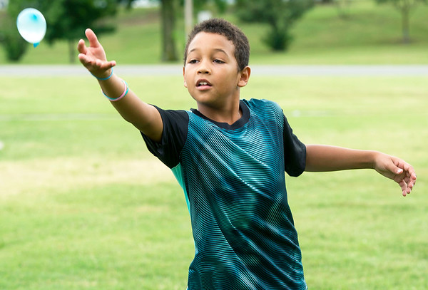 Nine-year-old Aiden Scourten tosses to his partner during a water balloon toss on Saturday at Ewert Park during the second day of Emancipation Days.<br /> Globe | Laurie Sisk