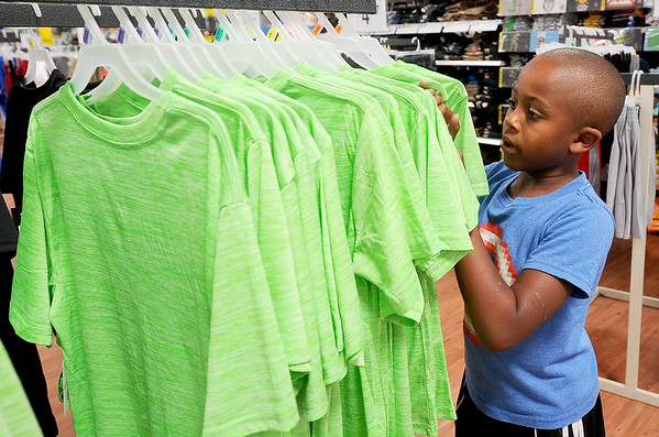 Eight-year-old Jet Steig, of Mound Valley, Kan., checks out new school clothes on Saturday at the Webb City Wal-Mart. With two other siblings in the family, it was worth the family's drive to Missouri to save on school clothes and supplies on the tax-free weekend.<br /> Globe | Laurie Sisk