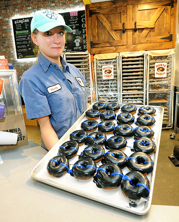 Hurts Donut's Jordan Weston holds a tray of Thin Blue Line donuts on Thursday at the store. The donuts are being sold to help the family of slain Clinton police officer Gary Michael. As of midday Thursday, the store had raised more than $2,000 for Michael's family.<br /> Globe | Laurie Sisk
