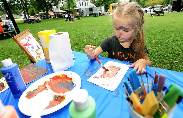 """Budding artist Riley Thurlow, 4, paints a wall switch plate and her face at the Carthage Water and Electric Plant's """"Come paint"""" booth in Central Park on Friday during Carthage's Food Truck Friday.<br /> Globe 