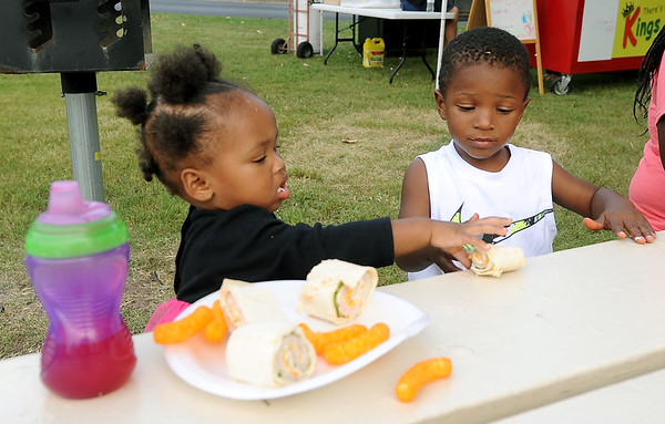 from the left: Jaedah Dawson, 1, shares part of her plate with Jayceon Caldwell, 2, on Saturday during the annual Emancipation Park Days at Ewert Park.<br /> Globe   Laurie Sisk