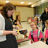 Kindergarten teacher Nicole Thorn, left, accepts a large wooden pencil as a gift from triplets Addison and Lauren Harper on the first day of school on Thursday at Jefferson Elementary. In the background, Regan Harper gets acquainted with her teacher, Chelsey Junker as the triplets mother, Jayme Harper looks on.<br /> Globe | Laurie Sisk