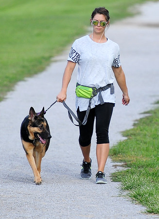 "Brianne Keener and her German Shepherd, ""Sadie"" enjoy an evening walk on Thursday at the Campbell Parkway walking trail. Keener said there are areas of the trail that have been washed out by heavy rains.<br /> Globe 