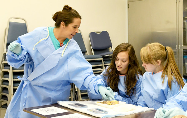 From the left: Freeman RN Carrie Coulson, left, points out the different components of a pig heart to Katherine Cooper, 16 and Jade Remington, 16 during the Freeman Health Academy on Thursday at Freeman East. <br /> Globe | Laurie Sisk