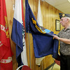 American Legion Post 13 veteran Richard Russell stands near flags representing each branch of service in the American Legion meeting room in Memorial Hall on Thursday.<br /> Globe | Laurie Sisk