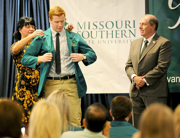 From the left: Missouri Southern Vice President of Academic Affairs Paula Carson helps Joshua Painter, of Joplin, with his green coat as Kansas City University of Medicine and Biosciences Provost Ed O'Connor looks on during a green coat ceremony and commitment signing on Saturday at MSSU.<br /> Globe | Laurie Sisk