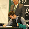 Garrett Dunn, of Reeds, signs his commitment papers as part of the inaugural class of the Yours to Lose Advanced Medical School Acceptance Program during a green coat ceremony and commitment signing on Saturday at MSSU.<br /> Globe | Laurie Sisk