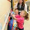 Front to back: Lauren and Addison Harper find hooks for their backpacks as their kindergarten teacher, Nicole Thorn looks on Thursday at Jefferson Elementary. The girls are two of a set of triplets, along with sister Regan Harper, who were born days before the May, 2011 tornado.<br /> Globe | Laurie Sisk