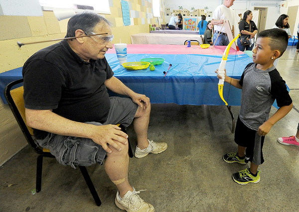 Five-year-old Alfredo Simpson smiles as he shoots a cup off the head of Pastor Greg Esselman during the Back-to-School Carnival on Saturday at First Presbyterian Church in Carthage. The event featured children's games, refreshments and more.<br /> Globe | Laurie Sisk