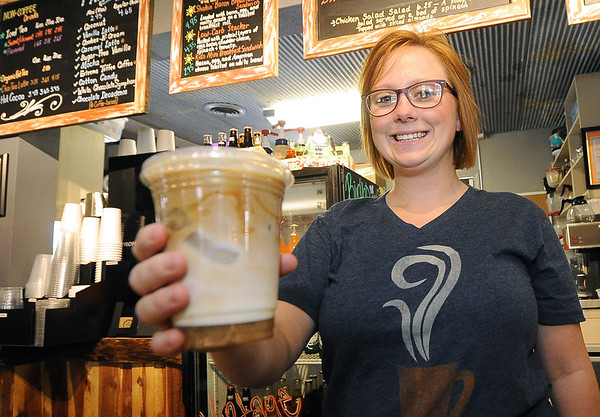 Angel Cholke, manager of MoJoe's Coffee in Neosho,  serves a caramel macchiato and a friendly smile on Saturday at the coffee shop. The City of Neosho has seen a dramatic increase in sales tax revenues lately.<br /> Globe | Laurie SIsk