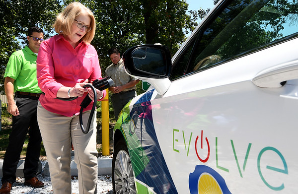 Wildcat Glades Conservation and Audubon Center Developmental Assistant Robin Standridge checks out the new electric vehicle charging station during ribbon cutting ceremonies on Friday at Wildcat Glades. To the left is Empire District Vice President of Customer Experience Brent Baker. The dual charging station is part of Empire's EVOLVe, an incentive program that encourages the use of electric vehicles.<br /> Globe | Laurie Sisk