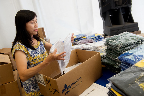 Globe/Roger Nomer<br /> Thuthao Nguyen, Houston, prepares a shirt vending table for Marian Days in Carthage on Tuesday.