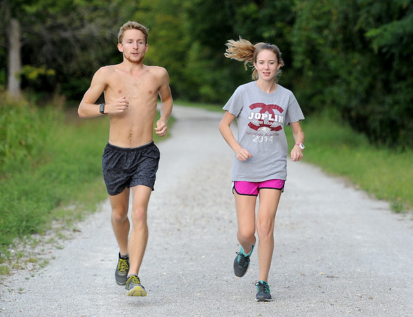 From the left: Pittsburg State distance runner Alex Burson and former Joplin High School and Missouri Southern runner Meggi Augustosky enjoy a run on the Frisco Trail on Thursday night.<br /> Globe | Laurie Sisk
