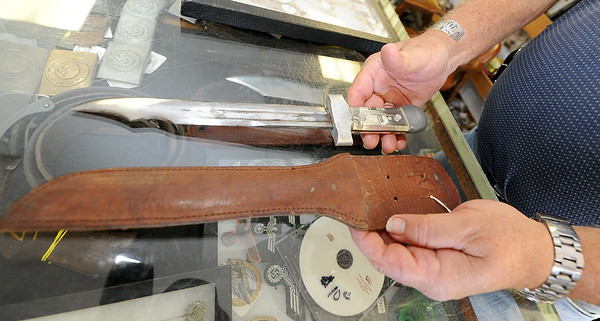 "Longtime collector W.G. ""Trip"" Triplett, of Circle T Collectibles in Carl Junction, holds a theater knife crafted from a bayonette by a U.S. service member. The knives, made in World War II, contained photos of loved ones under a plexiglass handle. <br /> Globe 