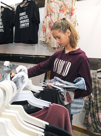 Amber Thurman, 14, checks out apparel while shopping at One 24 Boutique in Neosho on Saturday afternoon. The City of Neosho has seen a dramatic increase in sales tax revenues lately.<br /> Globe | Laurie SIsk