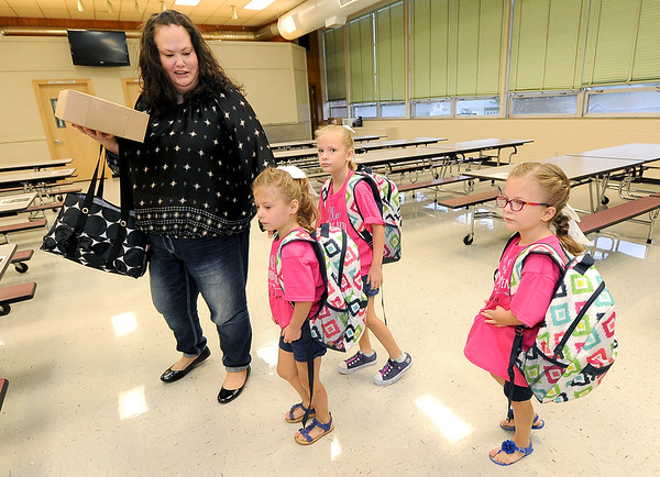 From the left: Jayme Harper leads her triplets, Lauren, Regan and Addison into the cafeteria on their first day of school on Thursday at Jefferson Elementary.<br /> Globe | Laurie Sisk