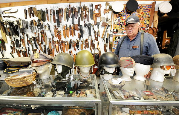 "Longtime collector W.G. ""Trip"" Triplett, of Circle T Collectibles in Carl Junction, stands near a variety of military head gear from across the globe. Triplett began collecting Native American and military artifacts 71 years ago and has countless items at his store and his home.<br /> Globe 