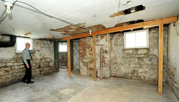 Brad Belk, director of the Joplin Museum Complex, walks Tuesday in the basement near what once served as a mortuary in the Schifferdecker House.<br /> Globe | Laurie Sisk