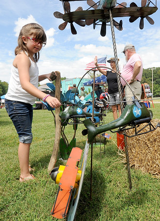 Tessa Larkin, 9, of Granby, checks out a helicopter mobile at the Surplus USA booth during the Four States Armed Forces Music Festival on Saturday at Morse Park in Neosho. Proceeds from the event will benefit area veteran's organizations and active duty service members and their families.<br /> Globe | Laurie Sisk