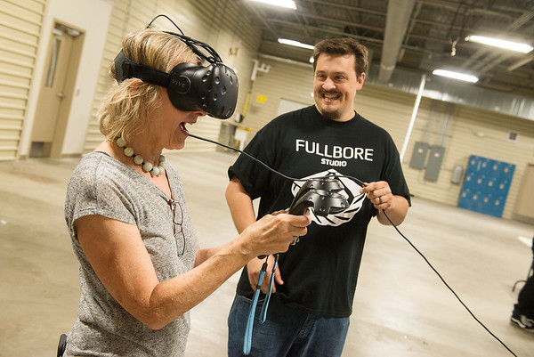 Globe/Roger Nomer<br /> Ben McNally helps Cleo Copeland with a virtual reality demonstration on Friday at the Joplin Area Chamber of Commerce Advanced training and Technology Center.