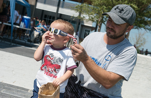 Globe/Roger Nomer<br /> Joe Ackerson, Joplin, helps fit his son Eli, 2, with eclipse glasses on Monday at the Joplin Public Library.