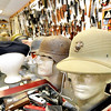 "A large selection of military headgear from around the globe rest on a showcase at Circle T Collectibles in Carl Junction. Owner W.G. ""Trip"" Triplett began collecting Native American and military artifacts 71 years ago and has countless items at his store and his home.<br /> Globe 