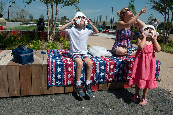 Globe/Roger Nomer<br /> Tiffany Seavy, Joplin, watches the eclipse with her children Elaina, 4, and Edward, 8, on Monday at the Joplin Public Library.