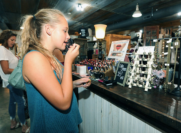 Piper Petronis, 13, checks out new lip color while shopping at One 24 Boutique in Neosho on Saturday afternoon. The City of Neosho has seen a dramatic increase in sales tax revenues lately.<br /> Globe | Laurie SIsk