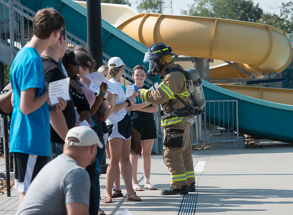 Globe/Roger Nomer<br /> A Joplin firefighter checks symptoms on mock victims on Wednesday at the Joplin Aquatic Center. Joplin emergency responders and the City of Joplin stages a chlorine spill at the pool as a drill.