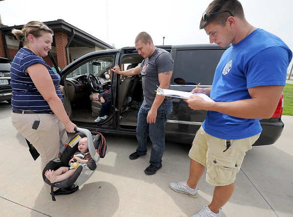 From the left: Caylee Gregory, of Carterville holds her son, Decklin Gregory, 7 months, as daughter Daeli Gregory, 4, catches an afternoon. Joplin firefighters Nick Patrick and Landon Osborn equipped mom and kids with a new carseat during a car seat check on Friday at Fire Station 13. The JFD and the Alliance of Southwest Missouri teamed together for classes and provided residents with about 40 new carseats.<br /> Globe | Laurie Sisk