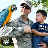 Army recruiter Samuel Harris and his two-year-old son Gabriel Harris get acquainted with Maxine, a blue and gold macaw owned by Pedro Perez during the National Night Out on Tuesday night at Schifferdecker Park. The annual national event encourages the building of relationships between emergency personnel and the communities they serve.<br /> Globe | Laurie Sisk